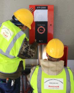 Countryside Alarms employees installing an IFP 2000 fire panel